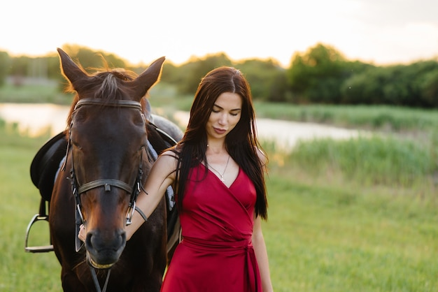 A young pretty girl in a red dress poses on a ranch with a thoroughbred stallion at sunset. love and care for animals.
