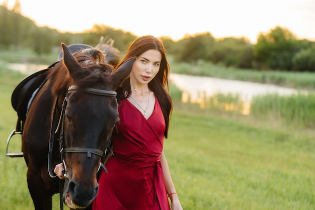 A young pretty girl in a red dress poses on a ranch with a thoroughbred stallion at sunset