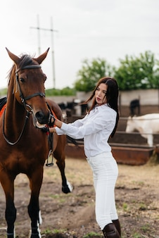 A young pretty girl rider poses near a thoroughbred stallion on a ranch