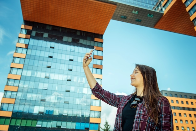 Young pretty girl in a shirt takes selfie on her smartphone and smiles. long-haired brunette with a phone on a city street, close-up.