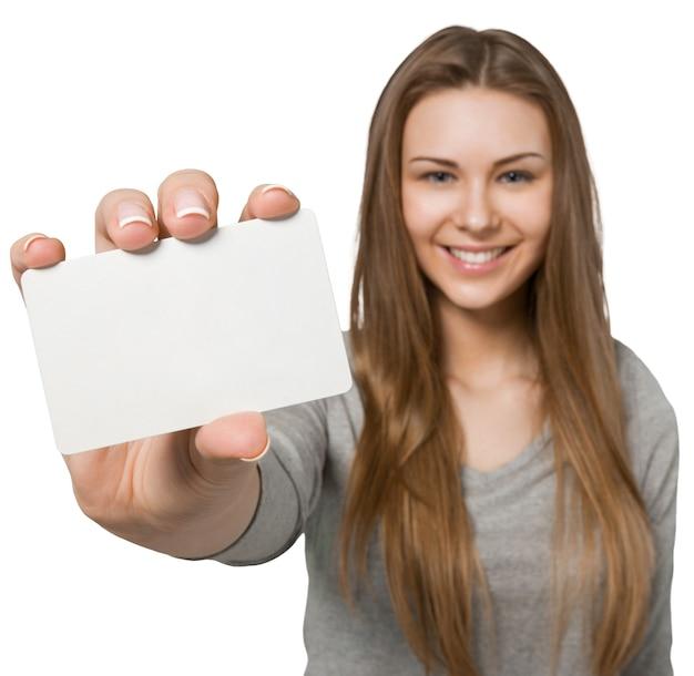 白で隔離の空白のカードを示す若いかわいい女の子