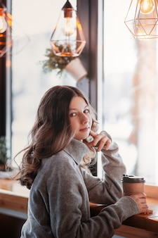 若いかわいい女の子は、コーヒーの紙コップと一緒にカフェに座っています