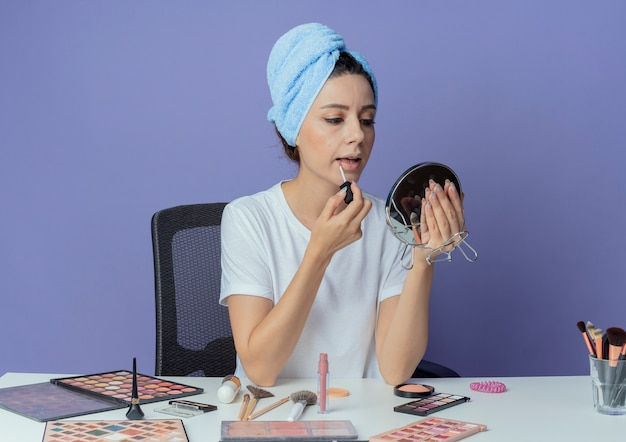 化粧ツールと頭にバスタオルを持って化粧台に座って鏡を見て、紫色の背景に分離されたリップグロスを適用する若いかわいい女の子 無料写真