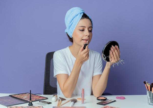 메이크업 도구와 메이크업 테이블에 앉아 머리를 잡고 거울을보고 보라색 배경에 고립 된 립글로스를 적용하는 젊은 예쁜 여자