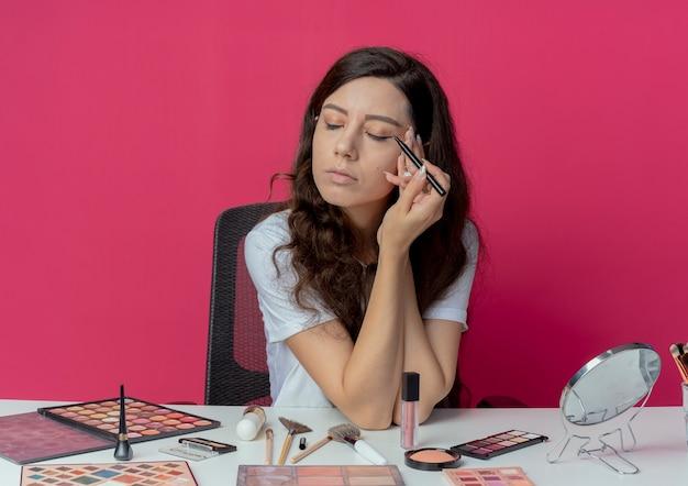 Молодая красивая девушка сидит за косметическим столом с инструментами для макияжа, применяя подводку для глаз и трогательно лицо с закрытыми глазами, изолированными на малиновом фоне