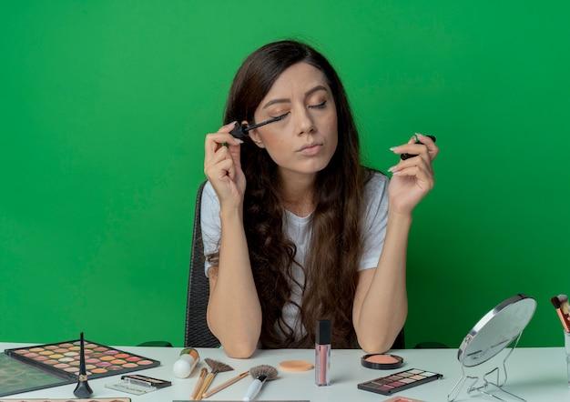 녹색 배경에 고립 된 닫힌 된 눈으로 마스카라를 적용하는 메이크업 도구와 메이크업 테이블에 앉아 젊은 예쁜 여자