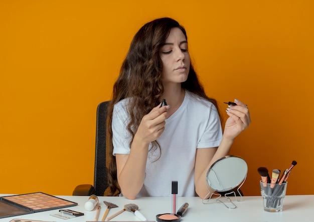 Молодая красивая девушка сидит за косметическим столом с инструментами для макияжа и смотрит на подводку для глаз, изолированную на оранжевом фоне