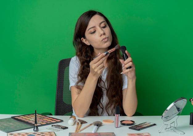 젊은 예쁜 여자 메이크업 도구를 들고 메이크업 테이블에 앉아 녹색 배경에 고립 된 메이크업 브러쉬를보고