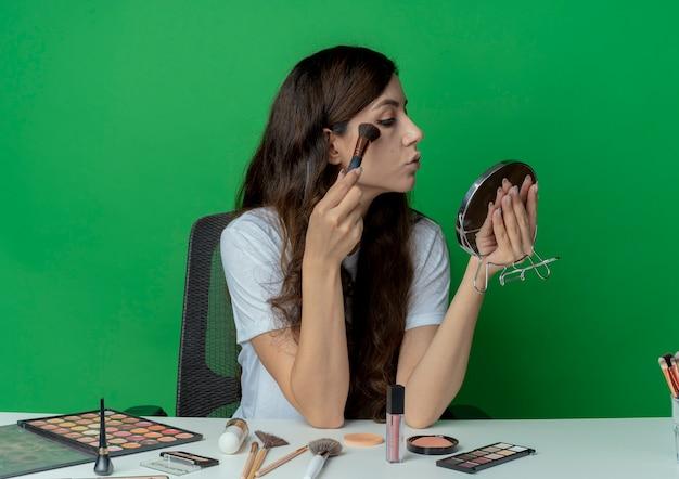 化粧台に座って、鏡を持って見て、緑の背景に分離されたブラシでパウダーを適用する化粧ツールで若いかわいい女の子