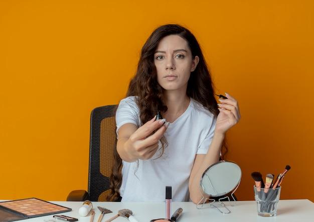 Молодая красивая девушка сидит за косметическим столом с инструментами для макияжа, держа и протягивая подводку к камере и глядя в камеру, изолированную на оранжевом фоне
