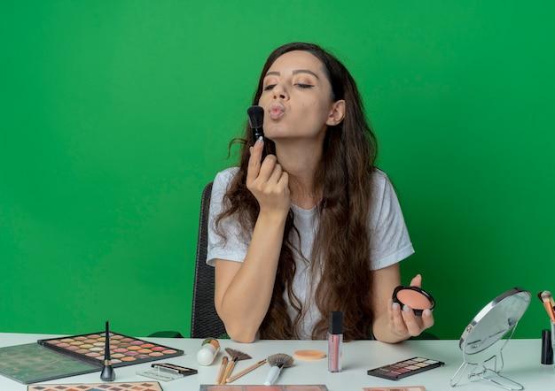 緑の背景に分離された赤面ブラシと赤面ブラシを見て、キスを身振りで示す化粧ツールで化粧テーブルに座っている若いかわいい女の子