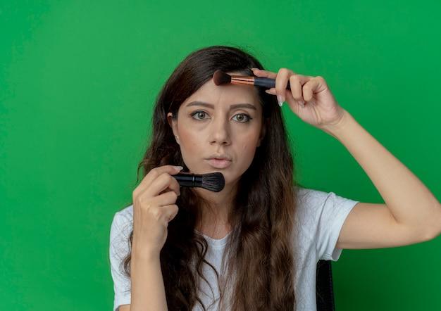 緑の背景に分離されたカメラを見て顔の近くに化粧ブラシを保持している化粧ツールで化粧テーブルに座っている若いかわいい女の子