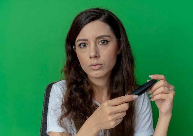 녹색 배경에 고립 된 카메라를보고 마스카라를 들고 메이크업 도구와 메이크업 테이블에 앉아 젊은 예쁜 여자