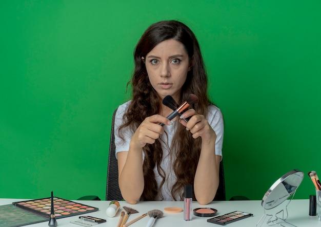 パウダーとチークのブラシを保持し、いいえを身振りで示して、緑の背景に分離されたカメラを見て化粧ツールで化粧テーブルに座っている若いかわいい女の子