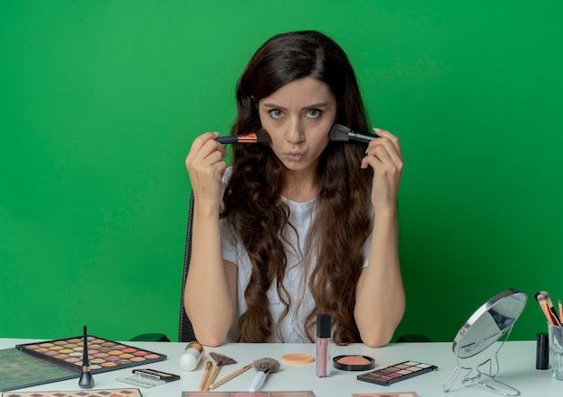 パウダーとチークのブラシを保持し、それらで頬に触れ、緑の背景に分離されたカメラを見て化粧ツールで化粧テーブルに座っている若いかわいい女の子