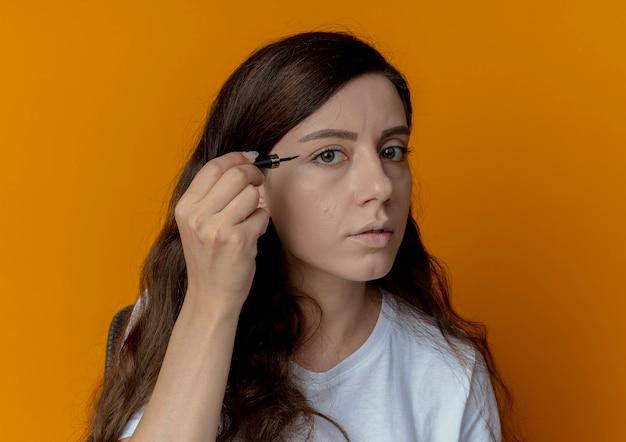 Молодая красивая девушка сидит за столом для макияжа с инструментами для макияжа, глядя в камеру, готовится применить подводку для глаз, изолированную на оранжевом фоне
