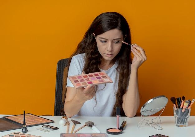 ミラーを見て、オレンジ色の背景に分離されたアイシャドウを適用する化粧ツールで化粧テーブルに座っている若いかわいい女の子
