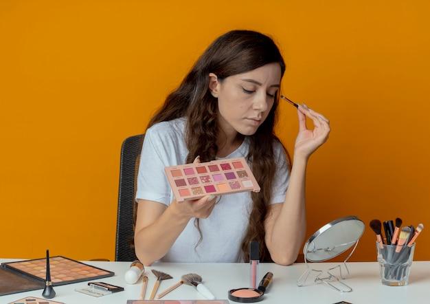 Молодая красивая девушка сидит за косметическим столом с инструментами для макияжа, глядя в зеркало и прикладывая тени для век с закрытыми глазами