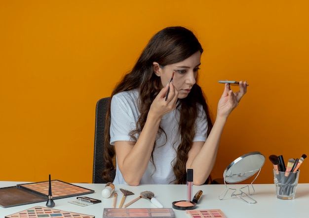 Молодая красивая девушка сидит за косметическим столом с инструментами для макияжа, глядя в зеркало и применяя тени для век
