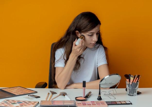 거울을보고 오렌지 배경에 고립 된 브러시로 기초를 적용하는 메이크업 도구로 메이크업 테이블에 앉아 젊은 예쁜 여자