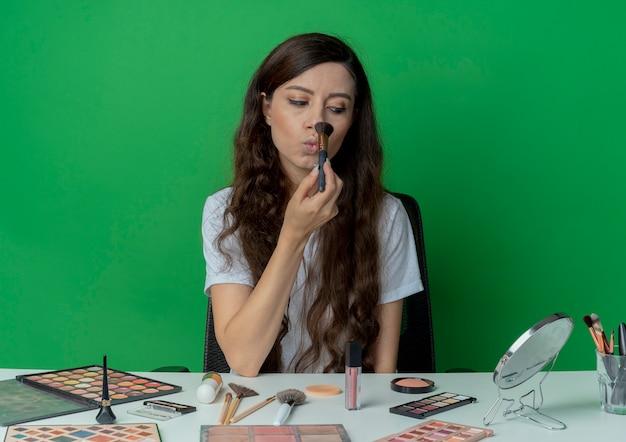 Молодая красивая девушка сидит за косметическим столом с инструментами для макияжа, глядя в зеркало, держа кисть для пудры и касаясь ею носа, изолированного на зеленом фоне