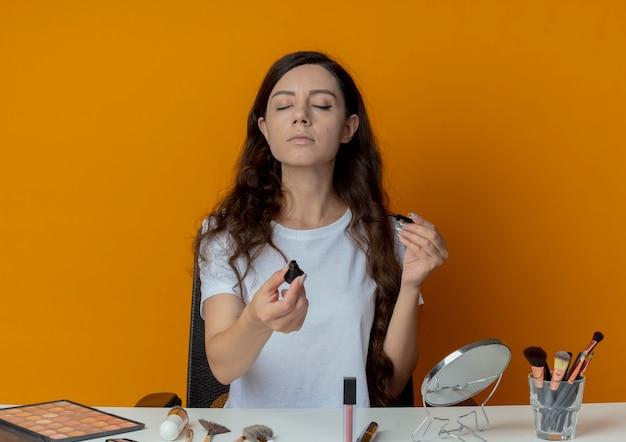 Молодая красивая девушка сидит за косметическим столом с инструментами для макияжа, протягивая подводку с закрытыми глазами, изолированными на оранжевом фоне