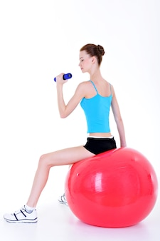 Young pretty girl sitting on the fitball and doing exercise with dumbbells