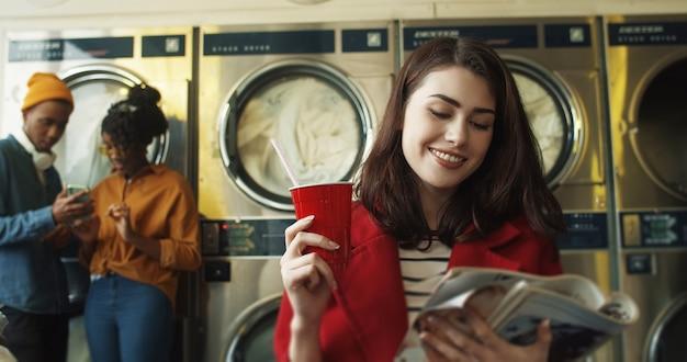 Молодая милая девушка сидя в комнате прачечной и читая журнал о моде пока потягивая питье с соломой. женщина с журналом в руках потягивает напиток в ожидании стирки одежды
