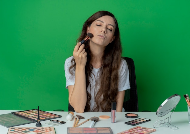 Young pretty girl sitting at makeup table with makeup tools applying blush on cheek with brush with closed eyes isolated on green background