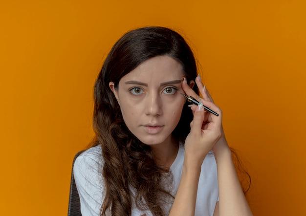 Giovane bella ragazza seduta al tavolo per il trucco con strumenti di trucco applicando eyeliner e toccando il viso guardando la telecamera isolata su sfondo arancione