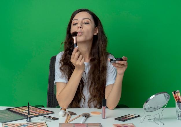 Giovane bella ragazza seduta al tavolo per il trucco con strumenti di trucco che tiene arrossire e soffia a pennello trucco isolato su priorità bassa verde