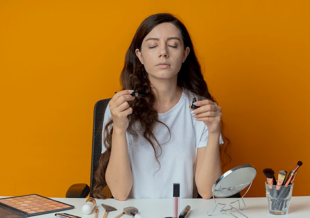 Giovane bella ragazza seduta al tavolo per il trucco con strumenti di trucco che tiene eyeliner con gli occhi chiusi isolati su priorità bassa arancione