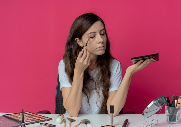 Young pretty girl sitting at makeup table with makeup tools holding eyeshadow palette looking at mirror and applying eye shadow with closed eyes isolated on crimson background