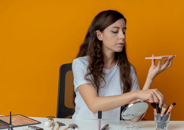 Giovane bella ragazza seduta al tavolo per il trucco con strumenti di trucco che tengono la tavolozza dell'ombretto e il pennello per il trucco isolato su priorità bassa arancione
