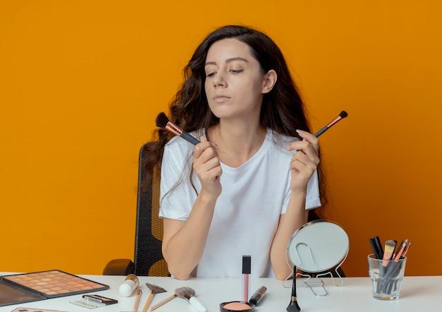 Giovane bella ragazza seduta al tavolo per il trucco con strumenti di trucco tenendo e guardando i pennelli trucco isolati su sfondo arancione