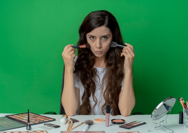 Young pretty girl sitting at makeup table with makeup tools holding powder and blush brushes and touching cheeks with them and looking at camera isolated on green background