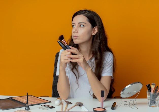 Young pretty girl sitting at makeup table with makeup tools holding powder brush and mascara and looking at side isolated on orange background