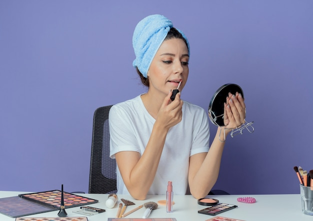 Giovane bella ragazza seduta al tavolo per il trucco con strumenti di trucco e con asciugamano da bagno sulla testa che tiene e guardando allo specchio e applicando lucidalabbra isolato su sfondo viola