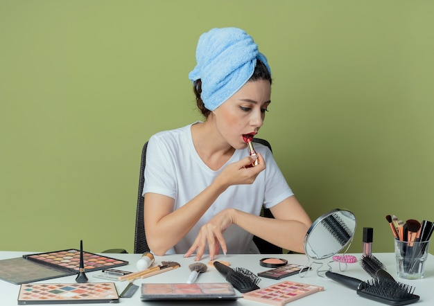 Giovane bella ragazza seduta al tavolo da trucco con strumenti per il trucco e con un asciugamano sulla testa guardando lo specchio e mettendo il rossetto rosso e toccando il tavolo sullo spazio verde oliva