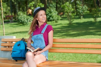 Young pretty girl sitting on the bench keeping a book.