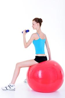 Молодая красивая девушка сидит на фитболе и делает упражнения с гантелями