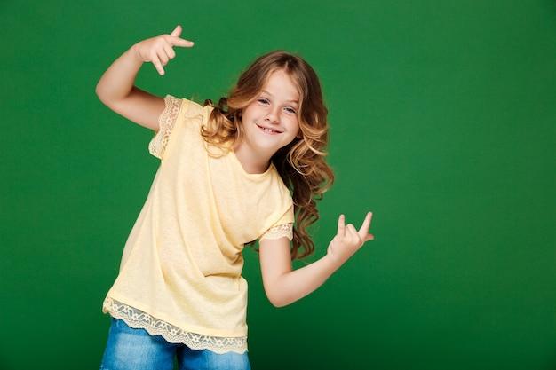 Giovane ragazza graziosa che sorride sopra la parete verde