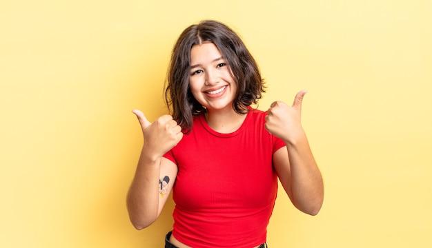 Молодая красивая девушка радостно улыбается и выглядит счастливой, чувствуя себя беззаботной и позитивной, подняв оба пальца вверх