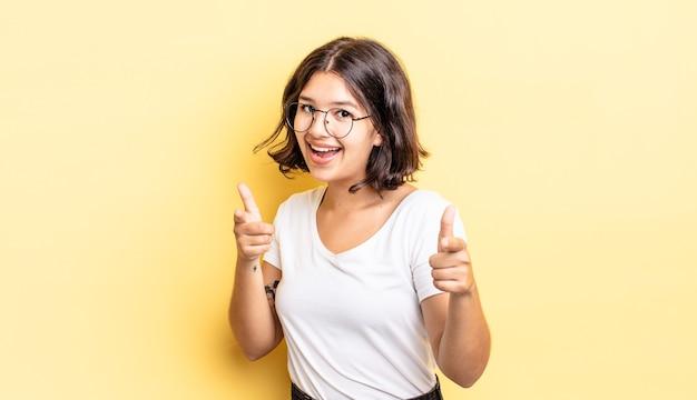 카메라를 가리키는 긍정적이고 성공적이고 행복한 태도로 웃고 있는 어린 예쁜 소녀, 손으로 총기 표시