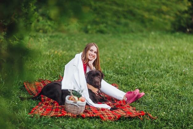 若いかわいい女の子は、毛布のカーペットの上に座っている彼女の茶色の犬と一緒に公園で彼女の時間を過ごします