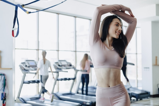 Young pretty girl in sportswear at the gym