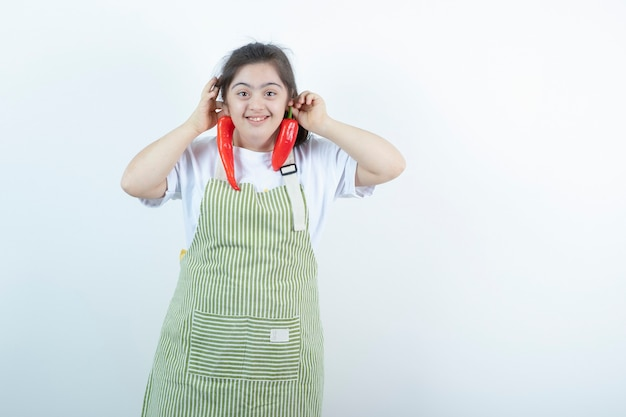 Young pretty girl standing in checkered apron and holding two red hot chili peppers .