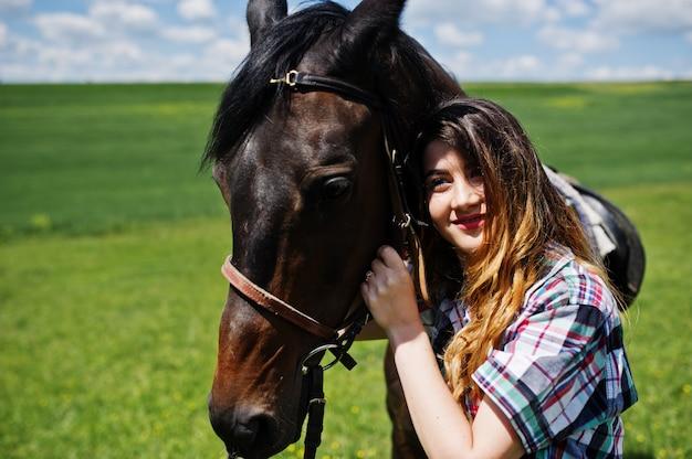 Молодое милое пребывание девушки с лошадью на поле на солнечном дне.