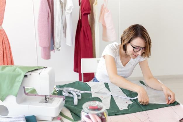Молодая симпатичная студентка учится у дизайнера одежды в колледже и делает свою первую диссертацию сидя