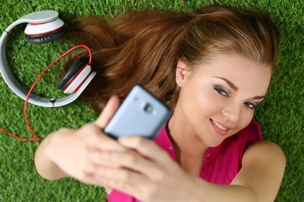 草の上に敷設する彼女のスマートフォンでセルフポートレートを取る若いきれいな女の子。顔に焦点を当てる